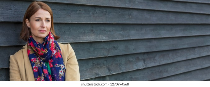 Attractive thoughtful or sad middle aged woman outside panoramic