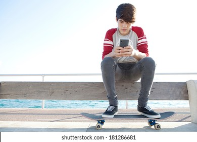 Attractive and thoughtful teenager boy relaxing with a skateboard and sitting down on a bench by the sea, holding and using a smartphone for networking during a sunny day, outdoors.