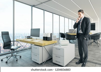 Attractive thoughtful young european businessman standing in contemporary office interior with city view. Research and executive concept.