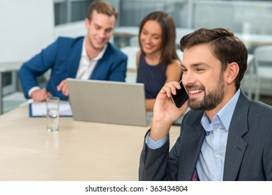 Attractive three business colleagues are taking part in a conference. They are sitting at the desk and smiling. The businessman is talking on the mobile phone. The man and woman are using laptop