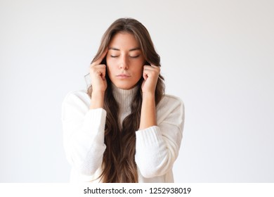 Attractive tired girl touching painful temples. Portrait of young Hispanic woman with closed eyes having headache. Isolated on white. Relaxing concept