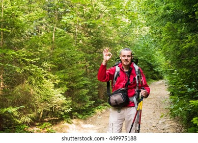 Attractive tourist with a big backpack trip tracking services and sticks shows sign OK on a mountain trail and smiling, happy traveler overcome a long way smiling,, adventure travel and discovery