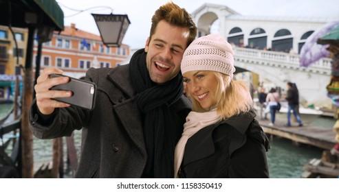 Attractive tourist couple take a selfie smiling by the Rialto Bridge