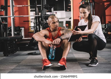 attractive trainer showing clipboard to african american sportsman sitting on floor