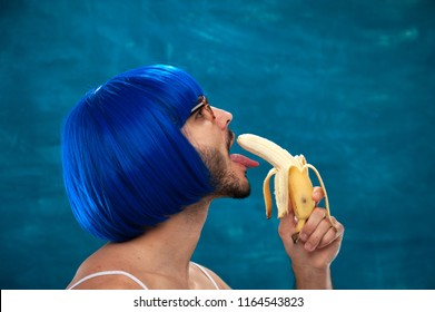 Attractive transsexual person wearing blue wig and female cloth eats banana. Place for text.