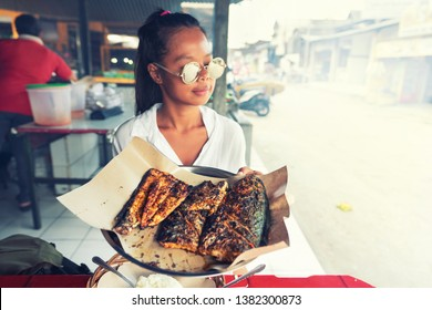Attractive travel woman enjoy seafood breakfast on a tropical beach Jimbaran on the background of fishing boats and nature landscape tropical island Bali, Indonesia