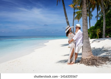 Attractive traveler couple in love enjoys their vacation time on a tropical beach with palm trees and turquoise ocean