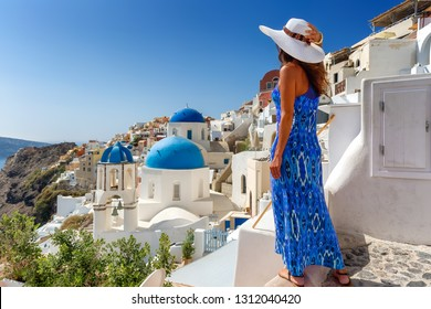 Attractive traveler tourist woman in blue dress enjoys the view to the white houses and blue churches at the village of Oia, Santorini, Greece