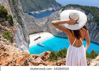 Attractive traveler woman stands on a cliff and enjoys the breathtaking view to the famous shipwreck beach, Navagio, on Zakynthos island, Greece