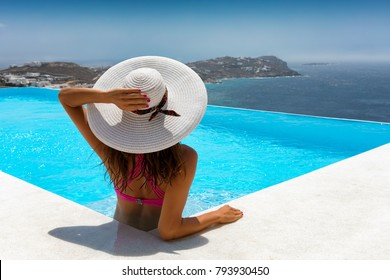Attractive traveller woman relaxes in a pool and enjoys her summer vacation time