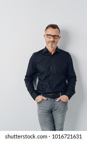 Attractive trendy casual middle-aged man wearing glasses standing with his hands in the pockets of his jeans in a relaxed stance over a white wall background