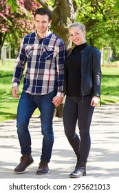 Attractive trendy couple enjoying a walk in the park strolling along a paved walkway hand in hand smiling at the camera