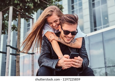 Attractive trendy dressed young couple sitting together on bench near skyscraper - pretty girl embraces her boyfriend.