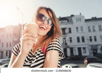 Attractive trendy young woman in sunglasses laughing as she drinking coffee and walking on the street with pink backpack