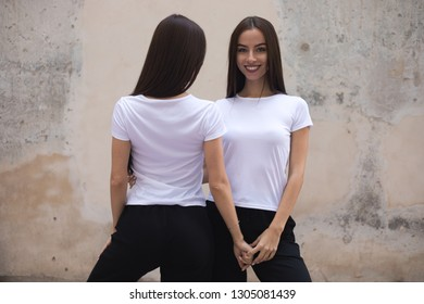 Attractive twin girls in white t-shirts.