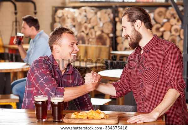 Attractive two men are greeting and shaking hands in pub. They are looking at each other and smiling. The bearded man is standing. His friend is sitting at table near glasses of beer and snack