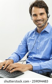 Attractive unshaven young man wearing a headset offering online chat and support on a client services of help desk as he types in information on his computer