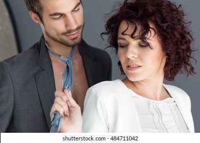 Attractive vamp woman provoke young man dragging his tie