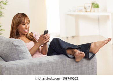 Attractive and vibrant Filipino female relaxing in living room in a home wearing a pink shirt and blue jeans on a grey chair.