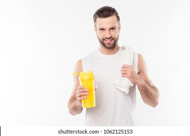 Attractive, virile, harsh, sportive man in white t-shirt holding yellow shaker in hands with gainer for mass and towel on his shoulder, ready for intensive training, isolated on white background