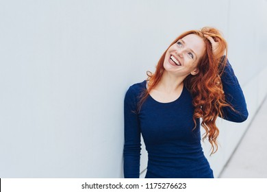 Attractive vivacious young redhead woman playing with her hair as she stands against a white exterior wall with copy space looking up with a happy smile