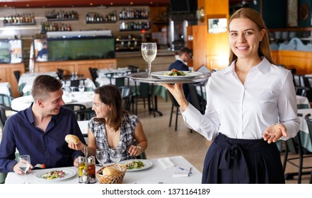 Attractive waitress holding tray with dish and glass of wine. Couple visitors on background