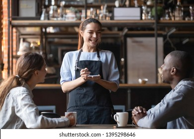Attractive waitress laughing at African American man funny joke, serving customers, diverse couple making order in cafe, coffeehouse female worker and multiracial visitors having fun