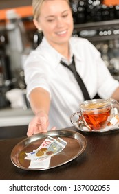 Attractive waitress taking tip in bar from tray euro