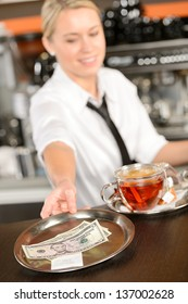 Attractive waitress taking tip in bar from tray american dollar