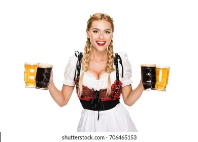 attractive waitress in traditional german costume holding beer glasses on Oktoberfest, isolated on white