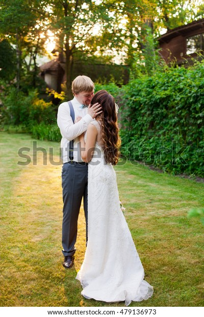 Attractive wedding couple is hugging in park