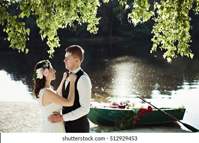 Attractive wedding couple is posing near boat with flowers