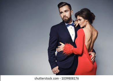 Attractive and well-dressed couple posing in studio. Woman in beautiful red dress and man wearing blue classical suit with bow tie.