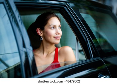An attractive well-dressed lady looking out a car window