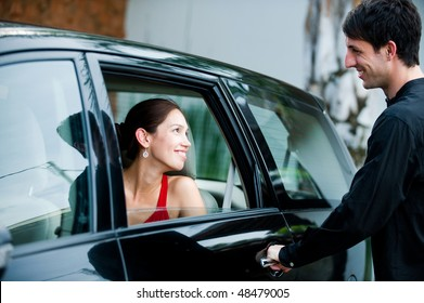 An attractive well-dressed man opening a car door for his partner outdoors