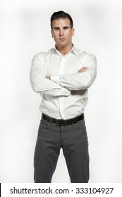 Attractive white male wearing a fitted white shirt and gray pants with a black belt while posing in a studio setting on a white background and looking at the camera with his hands crossed.
