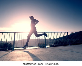Attractive wiry man jogging against to sun. Regular morning training at sea. Young sportsman jogging