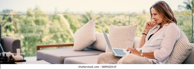 Attractive woman 40 years old in a white shirt sitting on a gray sofa working on a laptop on the terrace overlooking the green jungle on a bright sunny day.