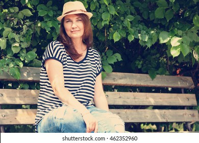attractive woman of 45 years on the bench in the park