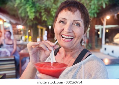 attractive woman of 50 years with a cocktail in hand, in a cafe