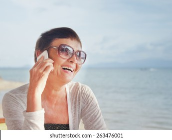 attractive woman of 50 years with a mobile phone at the beach cafe on the background of the sea