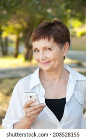 attractive woman 50 years in the park with a mobile phone