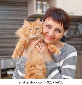 attractive woman of 50 years with a red cat in her arms at home