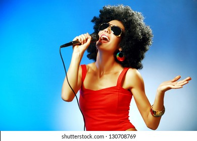 Attractive woman with afro hairstyle is singing expressively into the the microphone against blue background