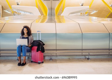 attractive Woman at the airport sitting and working with laptop