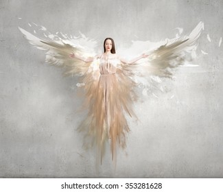 Attractive woman with angel wings on concrete background