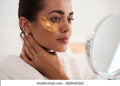Attractive woman applying anti-fatigue under-eye mask while looking at the mirror in the bathroom. Skin care girl touch patches of fabric mask under eyes to reduce eye bags