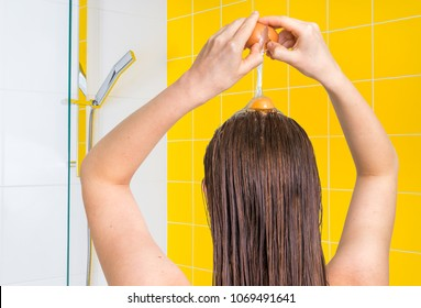 Attractive woman applying egg conditioner on her hair in bathroom