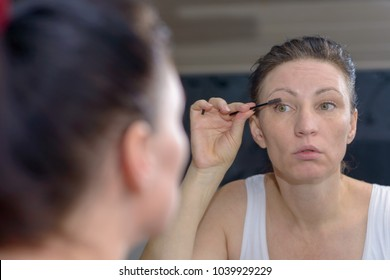 Attractive woman applying mascara to her lashes looking at her reflection in a bathroom mirror in a beauty and glamour concept