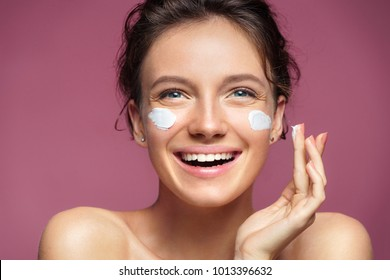 Attractive woman applying moisturizer cream on her face. Photo of young girl with flawless skin on pink background. Cosmetology